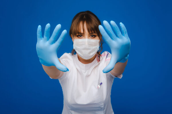 A girl doctor stands in a medical mask, isolated on a gray background