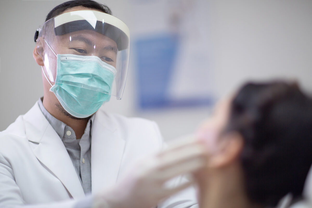 Male dentist wearing face mask, gloves and protective visor shiled as coronavirus safety precaution. Young woman on dental checkup appointment. New normal and healthcare concept