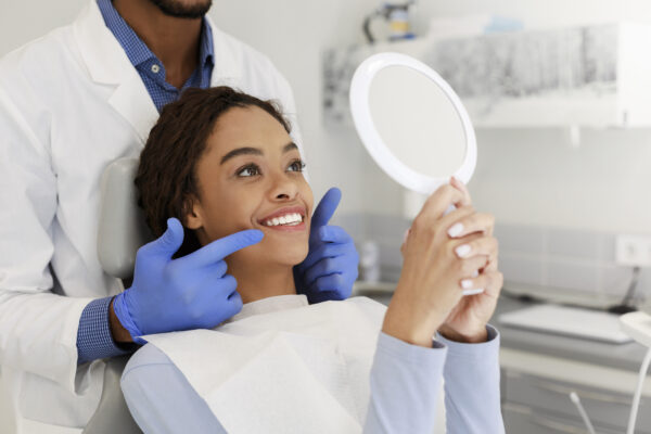 Attractive black lady checking her beautiful smile in mirror after stomatological treatment