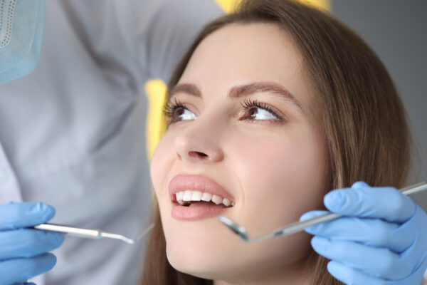 Doctor conducts dental examination of woman patient. Dental prosthetics and veneers concept